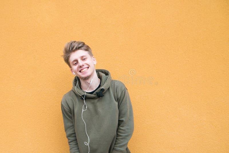 Den unga mannen står i gatan på bakgrunden av en orange vägg, lyssnar till musik och blickar på kameran royaltyfria bilder