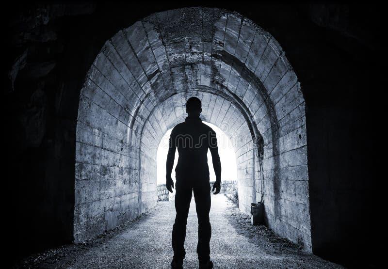 Den unga mannen står i mörk tunnel