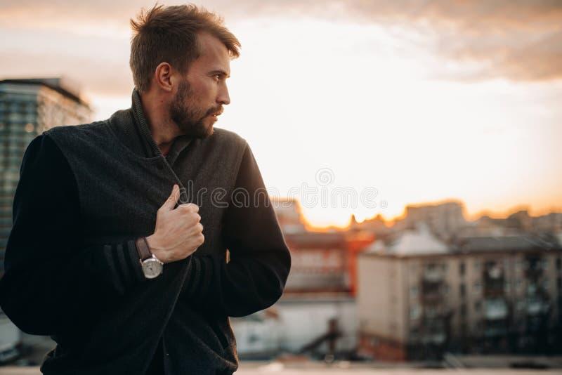 Den unga mannen står och tänker på hustaket mot bakgrund av skyskrapor och solnedgången royaltyfria foton