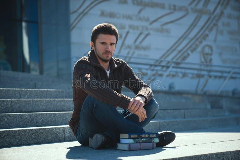 Den unga mannen studen läseboken utomhus i solig dag royaltyfri foto