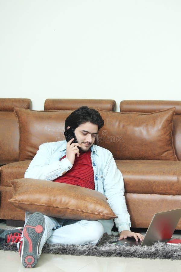 Den unga mannen talar telefonen med att använda bärbara datorn arkivbild