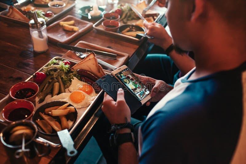 Den unga mannen tar en bild av hans mat för socialt nätverk Internetböjelsebegrepp Vänner har frukosten i kafé arkivbilder