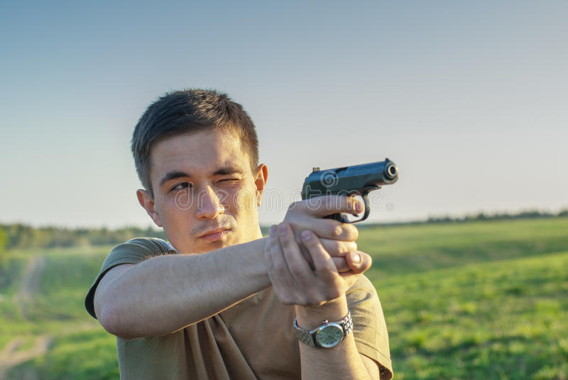 Den unga mannen tog syfte med pistolen arkivbilder