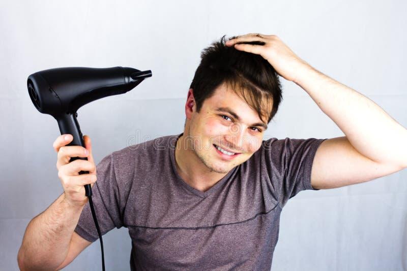 Den unga mannen torkar hår med en elektrisk fan Förbereda en frisyr för att gå till ett uteliv Tonåring som ler, medan han torkar royaltyfria bilder