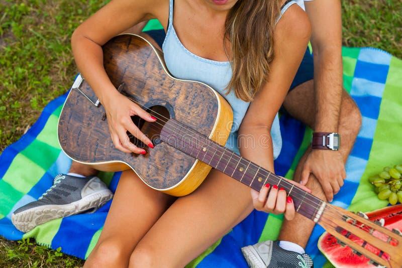 Den unga mannen undervisar hans flickvän att spela gitarren arkivfoton