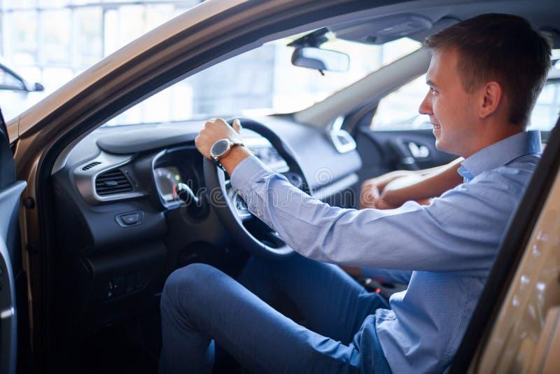 Den unga mannen väljer en ny bil Begreppet av att köpa en ny bil arkivfoto
