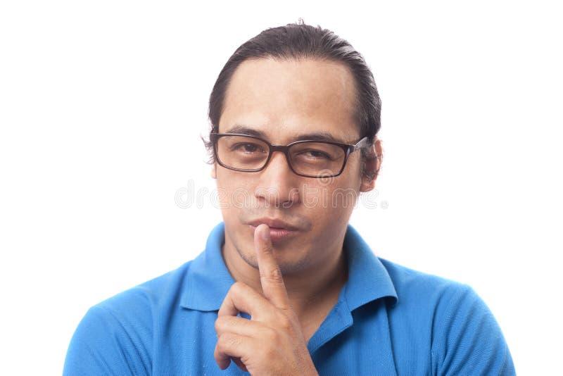 Den unga mannen visar att hyssja ner gest arkivfoton