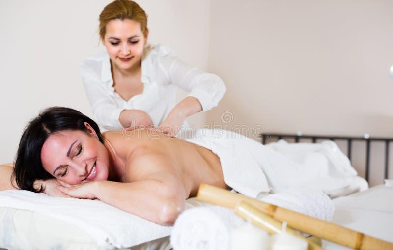 Den unga massösen gör sund massage av baksida och fransyskan till vuxna människan arkivbild