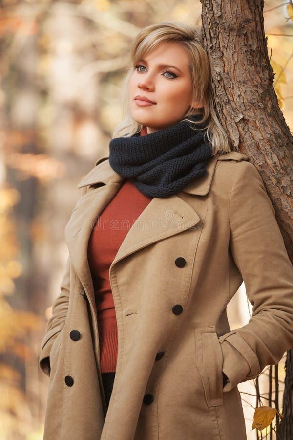 Den unga modekvinnan i beige lag i höst parkerar arkivbilder
