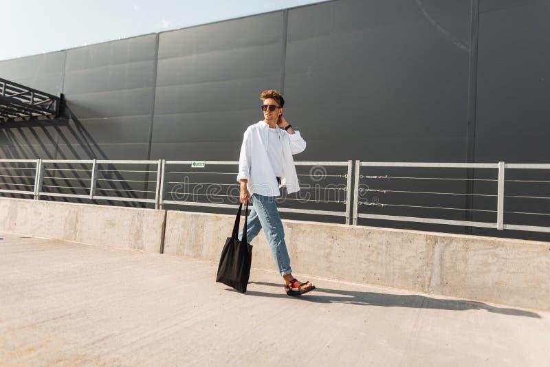 Den unga moderiktiga unga mannen går på staden på en solig dag Stilig hipstergrabb i trendig kläder i sommarskor med en påse fotografering för bildbyråer