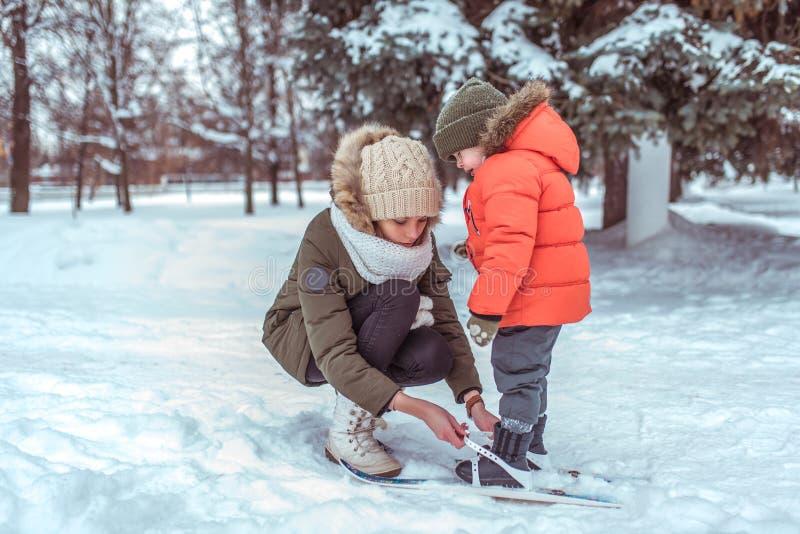 Den unga moderkvinnan fäster den skida pysen av 3-5 gamla år, son i vinterkläder I vinter i skogsemesterort var arkivfoto