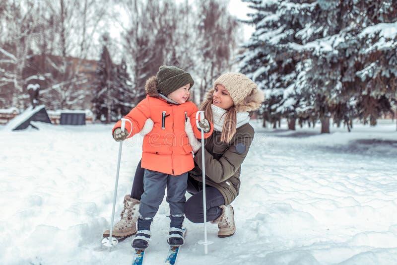 Den unga moderkvinnan rymmer lite pojken 3-5 år gammal, sonen i vinterkläder I vintern i träna i semesterorten royaltyfri bild