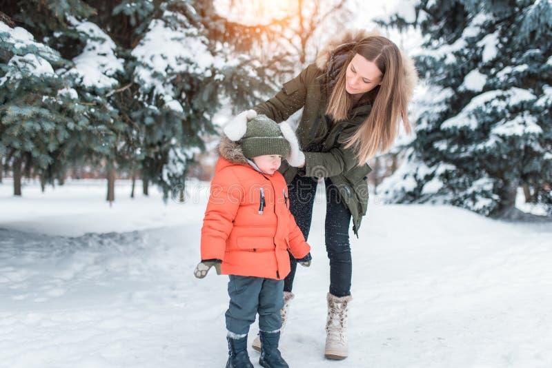 Den unga moderkvinnan skakar av snöhatten av lite pojken 3-5 gamla år, son i vinterkläder I vinter i royaltyfria bilder