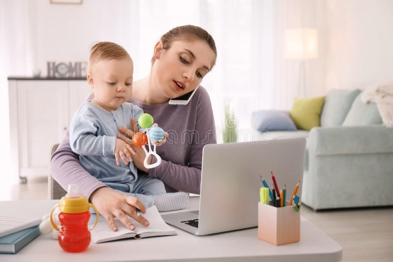 Den unga modern med behandla som ett barn samtal på telefonen, medan arbeta hemma arkivbilder