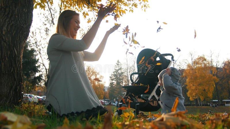 Den unga modern med henne som skrattar behandla som ett barn lite, kasta sidor i luften i höst parkerar royaltyfri foto