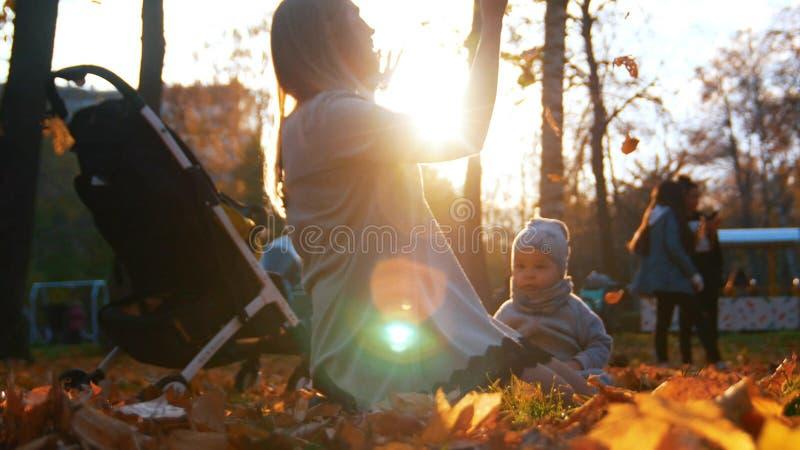 Den unga modern med hennes litet behandla som ett barn sittin på höstsidor i parkerar fotografering för bildbyråer