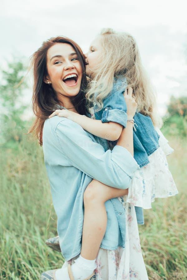 Den unga modern och dottern på grönt gräs arkivfoto