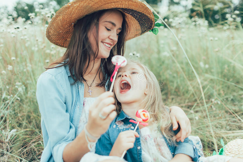 Den unga modern och dottern på grönt gräs arkivbild