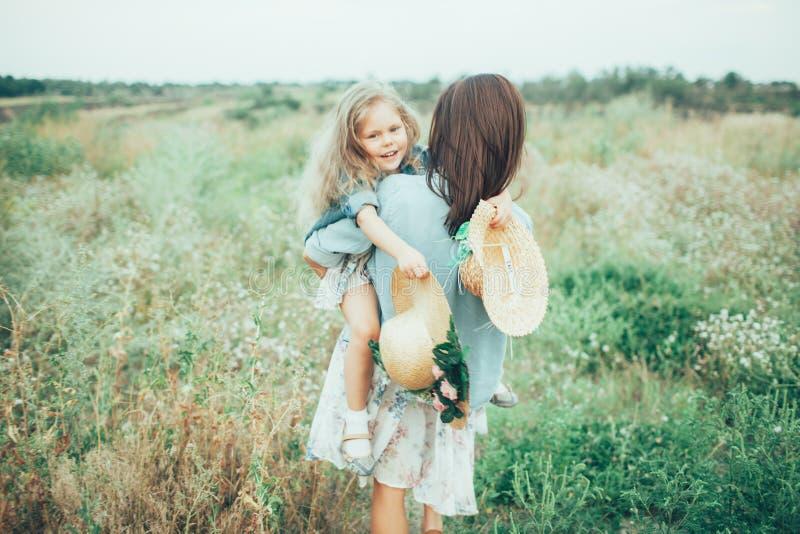 Den unga modern och dottern på grönt gräs arkivbilder