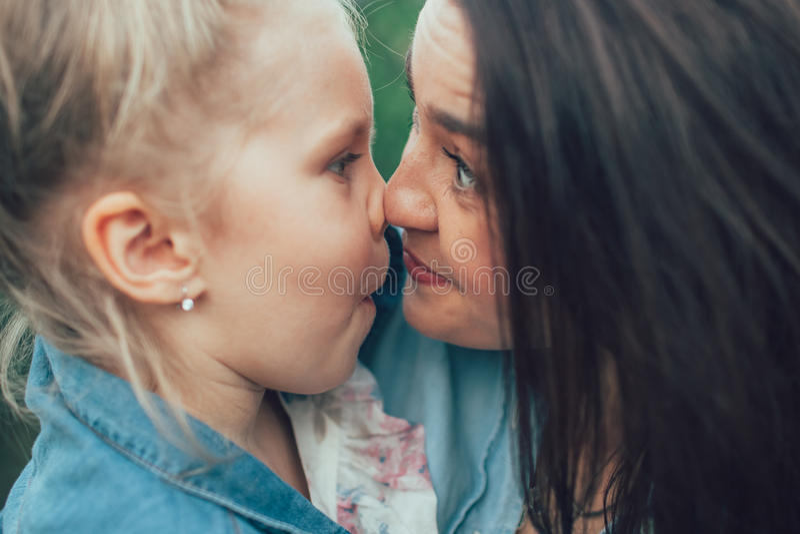 Den unga modern och dottern på grönt gräs arkivfoton