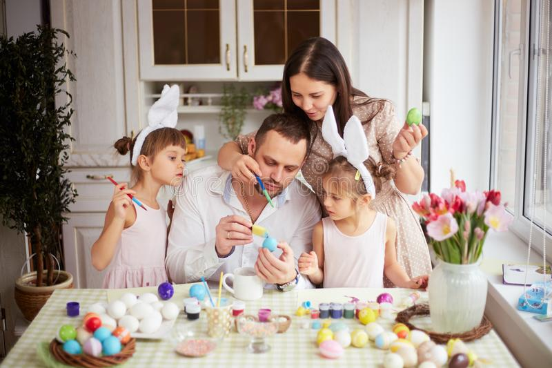 Den unga modern och fadern och deras två lilla döttrar med vita kanins öron på deras huvud färgar äggen för arkivfoto