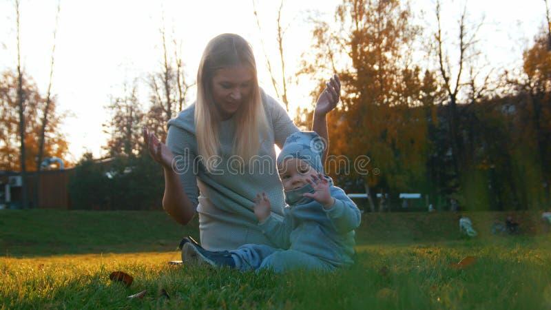 Den unga modern och hennes lite att behandla som ett barn att spela i höst parkerar Baby som ser i kameran arkivfoto