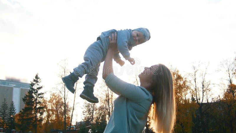 Den unga modern och hennes lite att behandla som ett barn att spela i höst parkerar behandla som ett barn holdingmodern arkivbilder