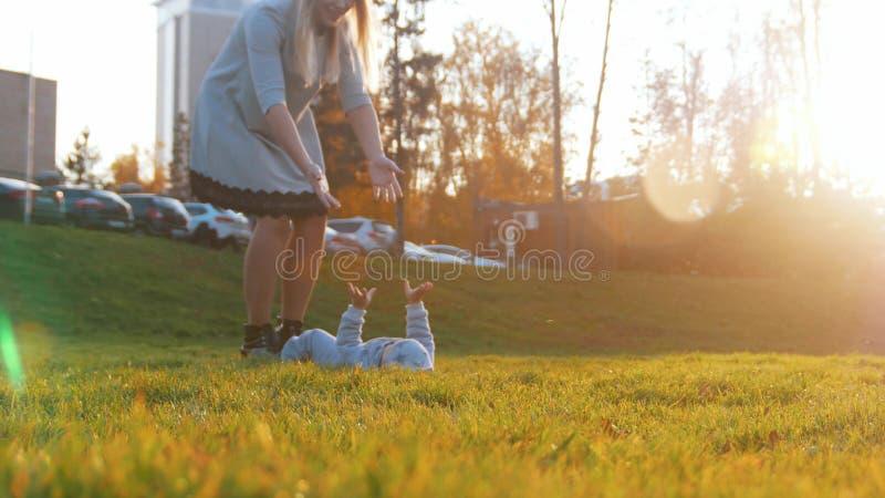 Den unga modern och hennes lite att behandla som ett barn att spela i höst parkerar Behandla som ett barn att ligga på gräset royaltyfri foto