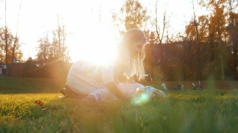 Den unga modern och hennes lite att behandla som ett barn att spela i parkerar Härligt solljus arkivfoton
