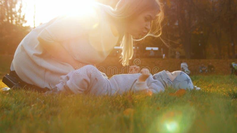 Den unga modern och hennes lite att behandla som ett barn att spela in parkerar Behandla som ett barn att ligga på gräset arkivbild