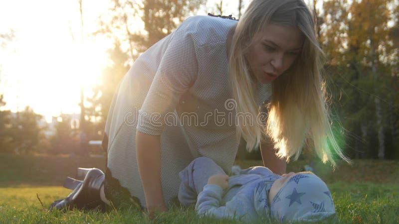 Den unga modern och hennes lite att behandla som ett barn att spela in parkerar Behandla som ett barn att ligga på gräset close u royaltyfri fotografi