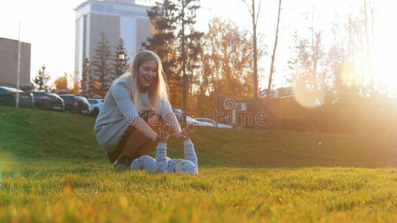 Den unga modern och hennes lite att behandla som ett barn att spela in parkerar Behandla som ett barn att ligga på gräset Att try royaltyfria foton