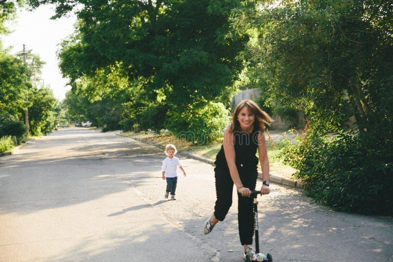Den unga modern rider en sparkcykel och lite en son bak henne arkivbilder