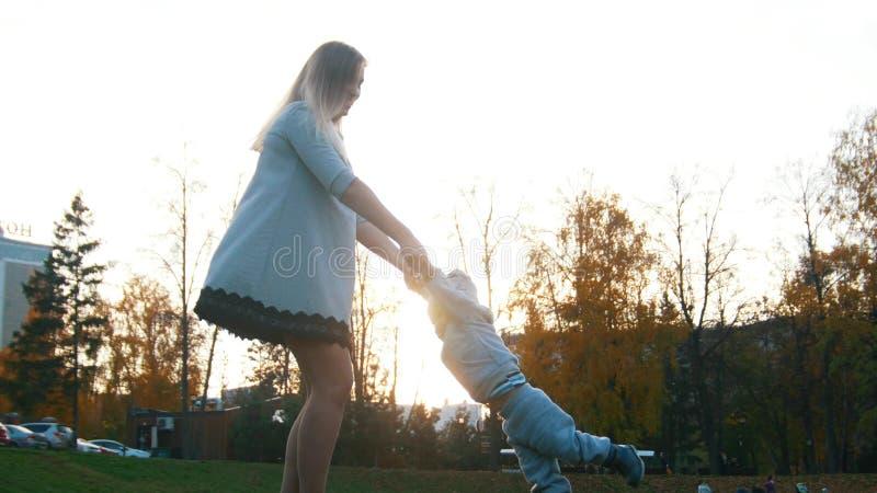 Den unga modern som omkring rotera hennes litet, behandla som ett barn och att rymma honom vid händer royaltyfria foton