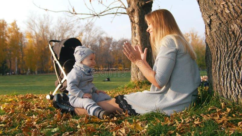 Den unga modern som spelar med hennes skratta som är litet, behandla som ett barn i höst parkerar fotografering för bildbyråer