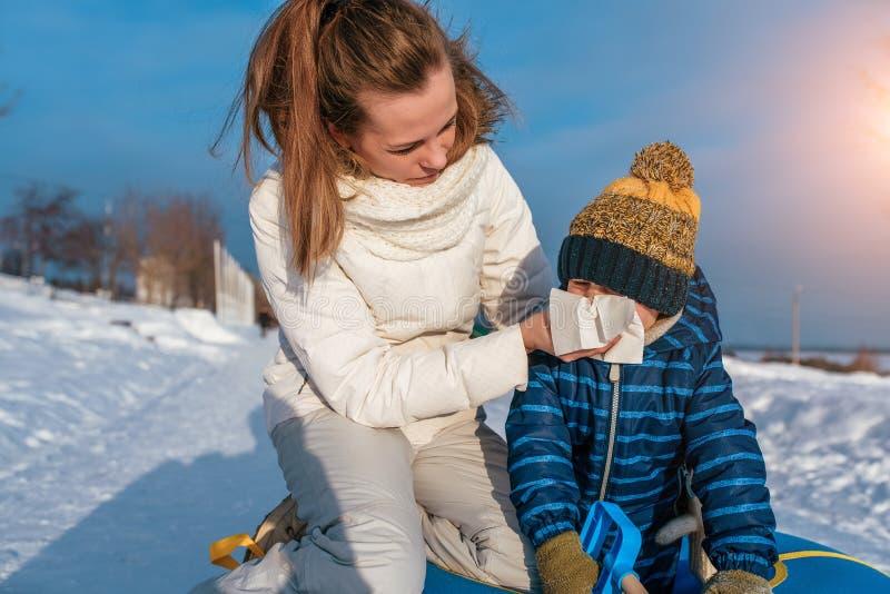 Den unga modern torkar det hennes snoret behandla som ett barn I vinter i den nya luften Begreppet av hälsa och barnavård Förkyln arkivfoto