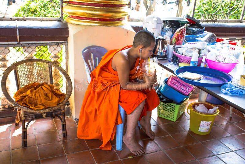 Den unga munken lyssnar till musik inom Wat Suan Dok Temple, Chiang Mai, Thailand royaltyfria bilder