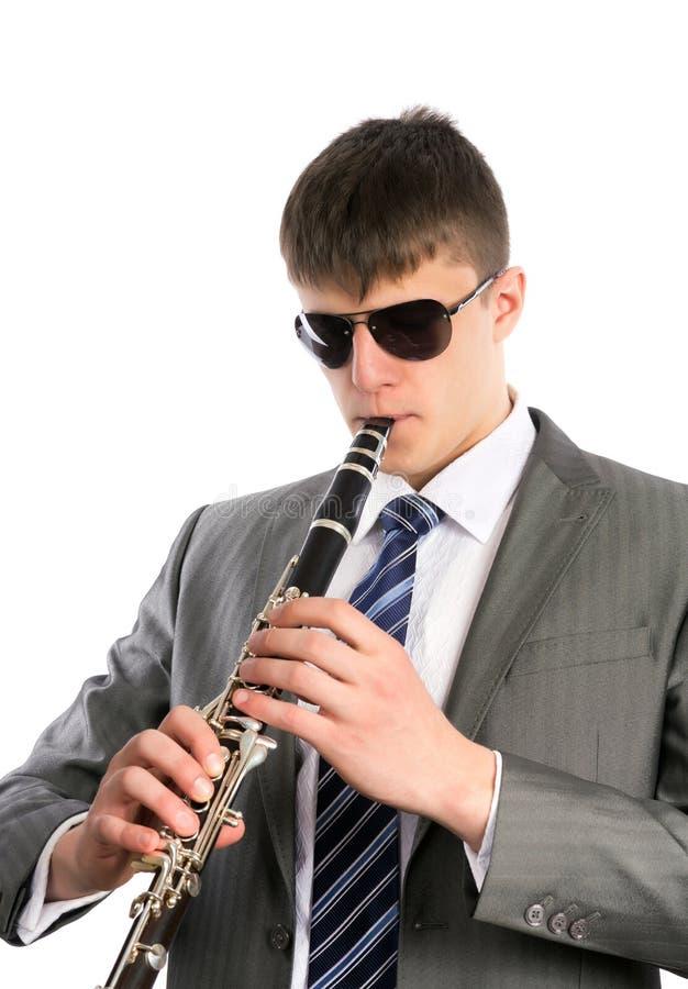 Den unga musiker leker klarinetten i solglasögon fotografering för bildbyråer