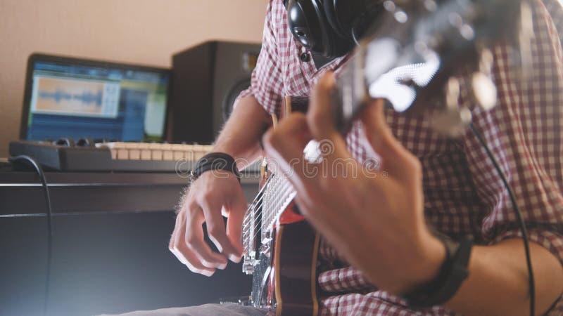 Den unga musikern komponerar och antecknar musik som spelar den elektriska gitarren genom att använda datoren och tangentbordet arkivbilder