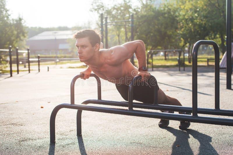 Den unga muskulösa manliga idrottsman nen som gör liggande armhävning, övar i parkera arkivfoto