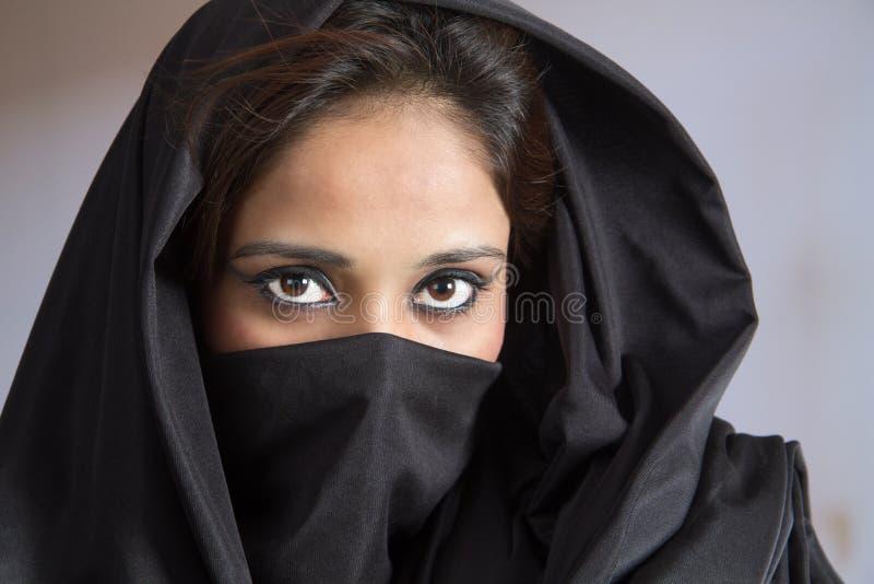 Den unga muslimska damen i svart kappa skyler hijaab royaltyfria bilder