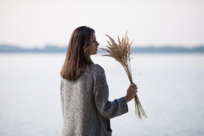 Den unga mycket härliga flickan med långt hår står vid sjön royaltyfria bilder