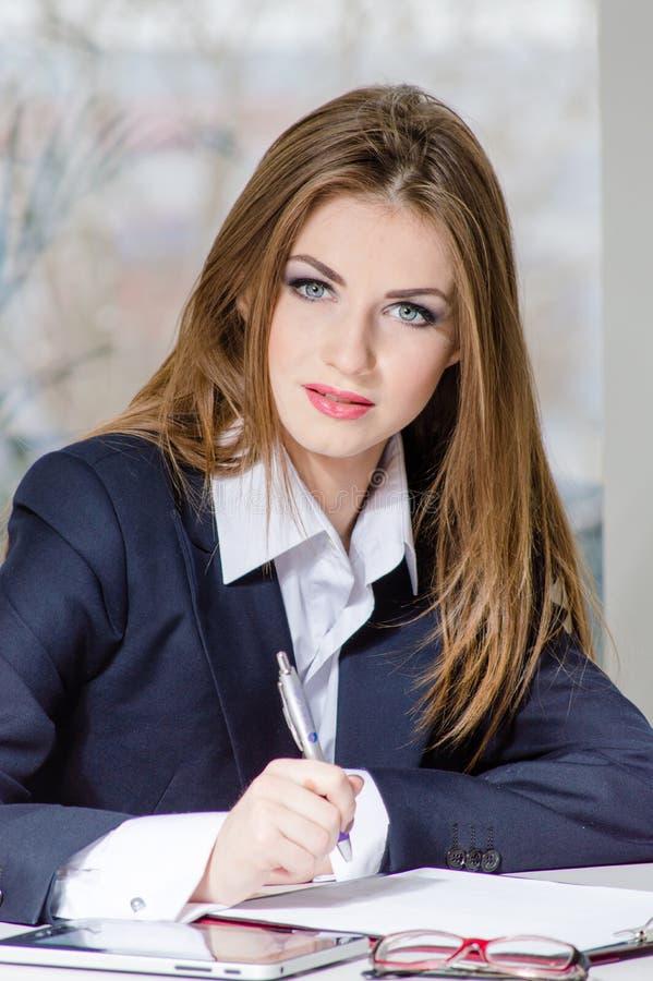Den härliga unga affärskvinnan på kontorsarbetet förlägger arkivbild