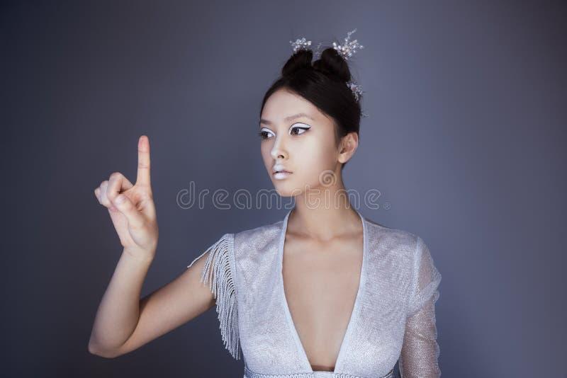 Den unga nätta asiatiska futuristiska kvinnan som trycker på en imaginär knapp, tömmer utrymme för knappar royaltyfri bild