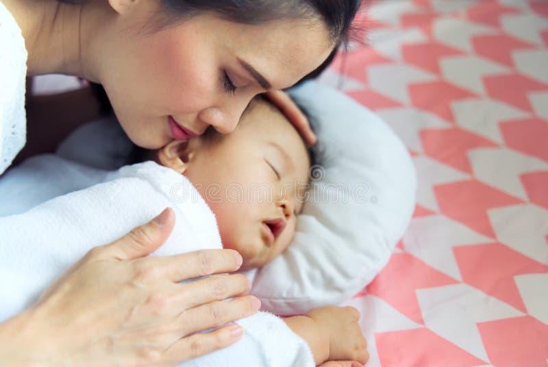 Den unga nätta asiatiska modern som kramar hennes sova som är gulligt, behandla som ett barn på sängen Modern som stänger hennes  royaltyfri fotografi