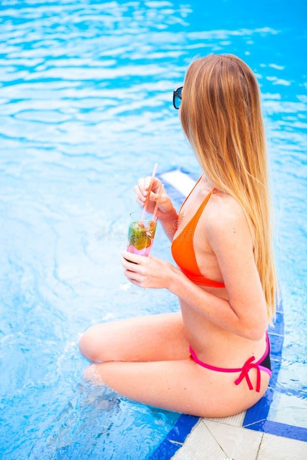 Den unga nätta blonda kvinnan i en orange bikini och solglasögon tycker om royaltyfri bild