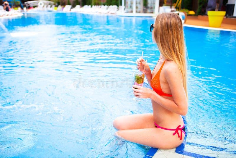Den unga nätta blonda kvinnan i en orange bikini och solglasögon tycker om arkivbild