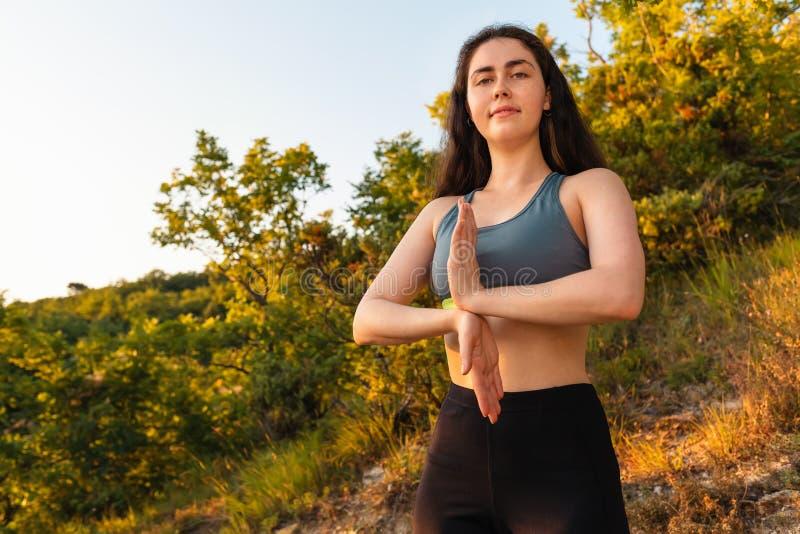 Den unga nätta brunettkvinnan som gör yoga i, parkerar eller skogen begreppet av kondition, yoga och sportar royaltyfri foto