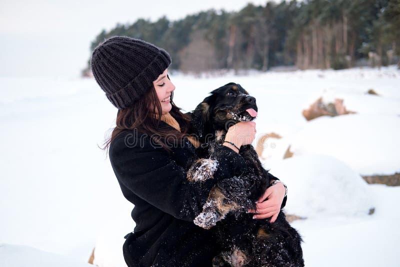 Den unga nätta caucasian kvinnan som rymmer hennes hund på händer, att spela som utomhus skrattar parkerar in arkivfoto