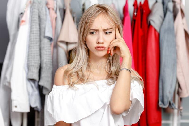 Den unga nätta flickabloggeren står med ett fundersamt uttryck på hans framsida på bakgrunden av kläder som hänger på a arkivbild